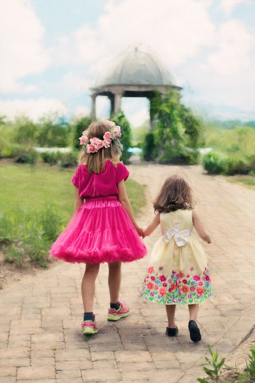 2 Girls in Pink Dress Standing on Brown Dirt Road