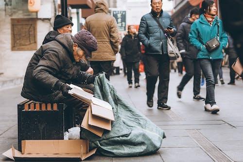 An Elderly Person Sitting By The Sidewalk