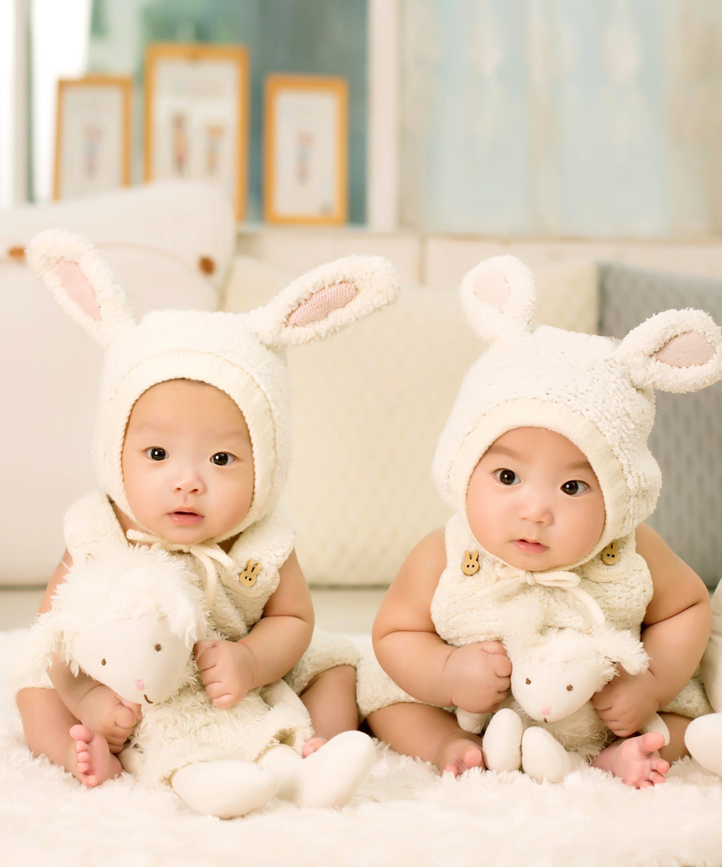 2 Babies Wearing White Headdress White Holding White Plush Toys