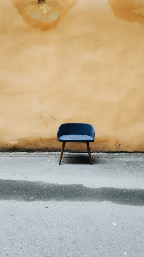 Blue and Black Chair Beside Brown Wall