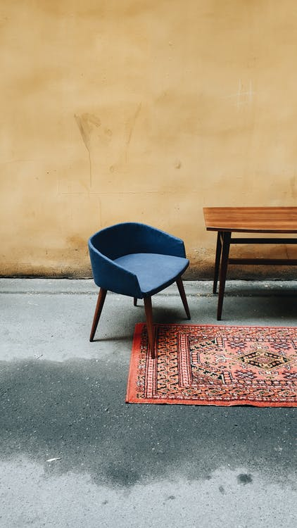 A Blue Chair  And Wooden Table In A Room