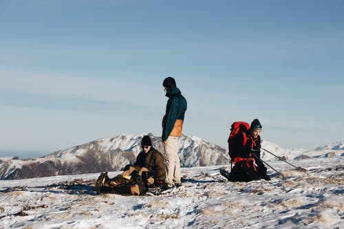 Group of travelers in outerwear with backpacks and hiking equipment resting on snowy ground during expedition against cloudless blue sky and mountain peaks