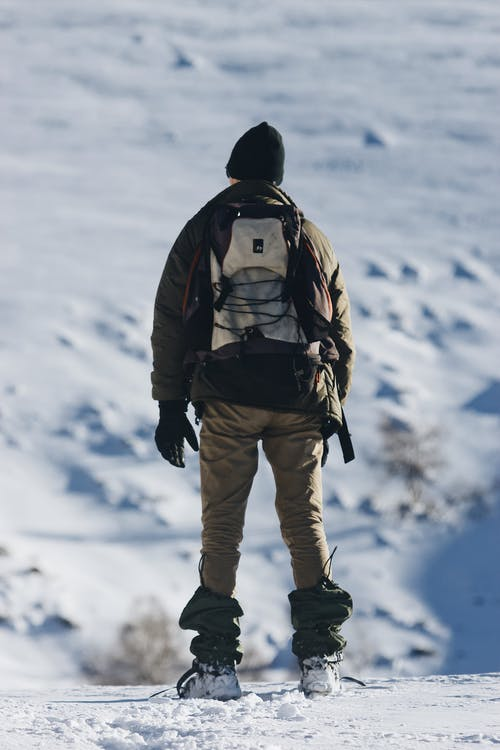 Unrecognizable traveler standing on snowy land against mountain ridge on sunny day