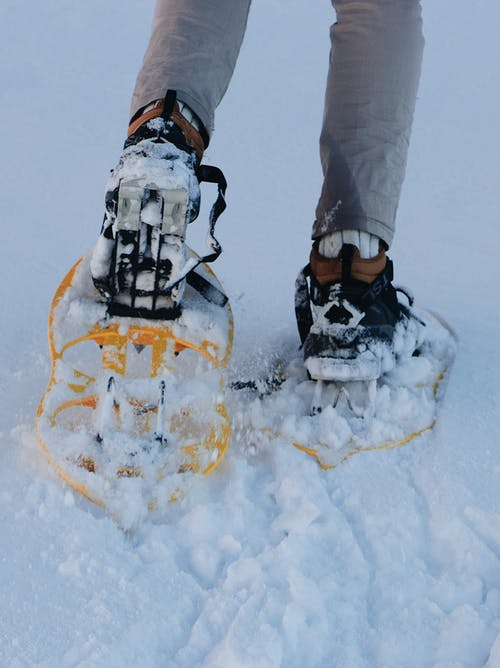 Crop faceless hiker in snowshoes walking on snowy ground during winter expedition in mountains