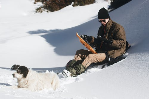 Man in Brown Jacket and Black Pants Sitting on Snow Covered Ground
