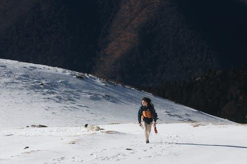 Anonymous hiker walking along snowy terrain in highland