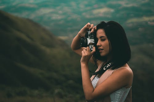 Woman Holding A Black Dslr Camera And Taking A Picture