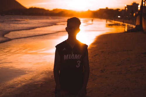 Man in Black vest Standing on Beach during Sunset