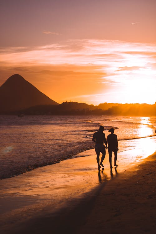Silhouette of Two People Walking on Beach during Sunset
