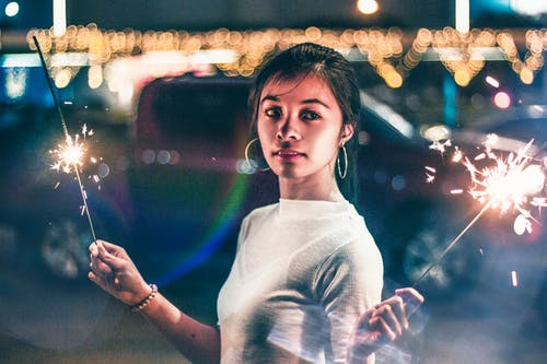 Woman in White Crew Neck Shirt Standing in Front of Lighted City Buildings during Night Time