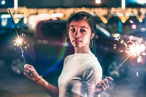 Frau Im Weißen Hemd Mit Rundhalsausschnitt, Das Vor Beleuchteten Stadtgebäuden Während Der Nachtzeit Steht