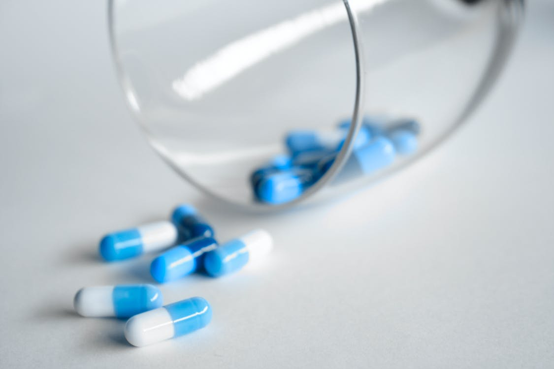 Depth Photography of Blue and White Medication Pill
