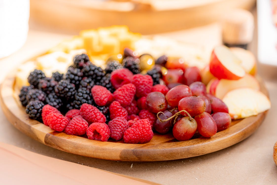 Red and Black Berries on Brown Wooden Plate