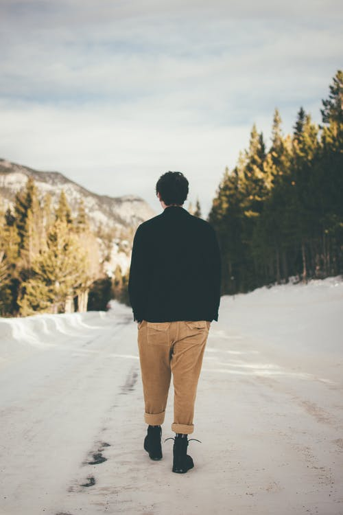 Photo of Person Walking on Snow Covered Ground