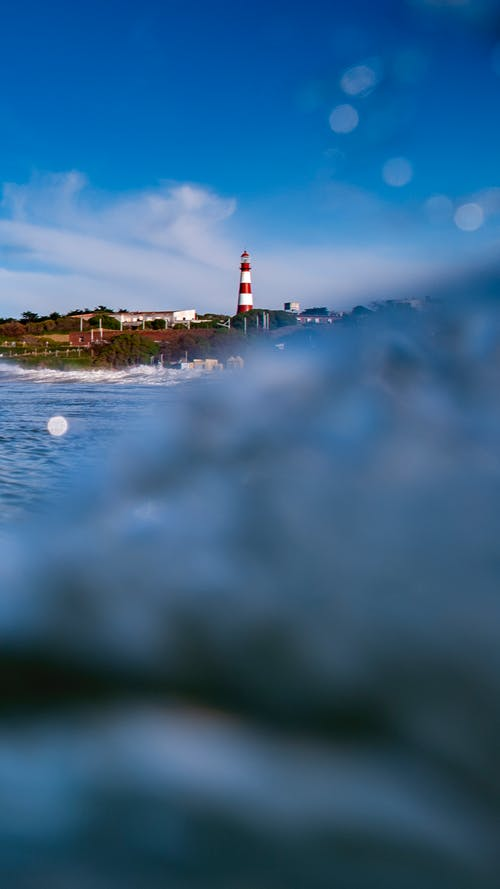 White and Red Lighthouse Near Body of Water Under White Clouds and Blue Sky