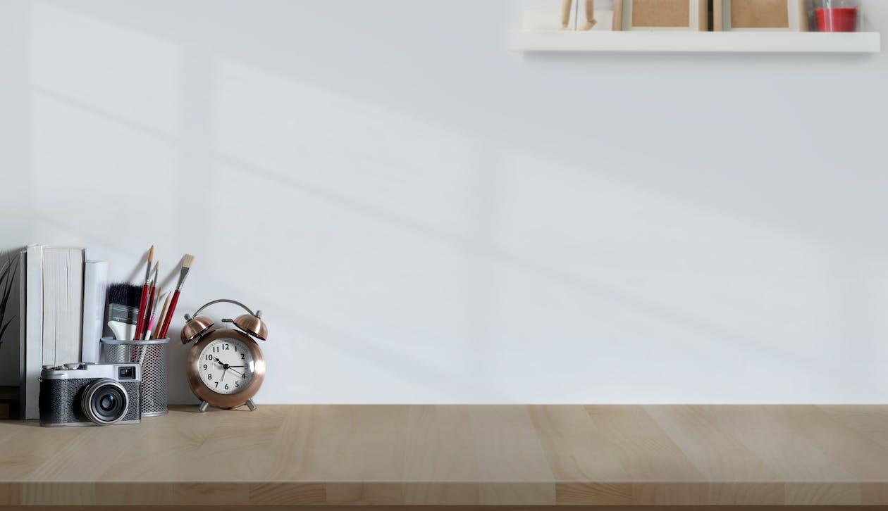 Alarm Clock And Analog Camera On Wooden Desk