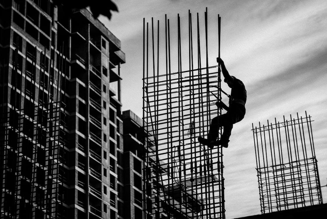 Silhueta De Homem Segurando Uma Estrutura De Metal