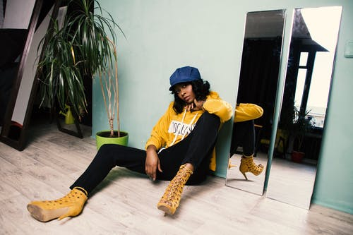 Woman in Yellow Jacket and Black Pants Sitting on the Floor