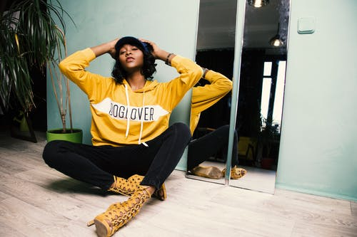Woman in Yellow Hoodie Sitting on The Floor