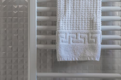 White Towel on White Wooden Rack