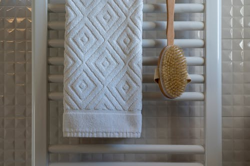 White Towel And Wooden Brush Hanging In The Bathroom