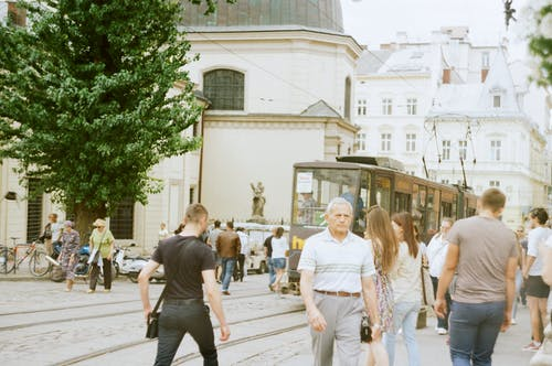 Crowded street with people walking near tramway in aged city with concrete buildings