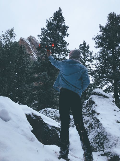 Man in Blue Jacket and Black Pants Standing on Snow Holding a Drone