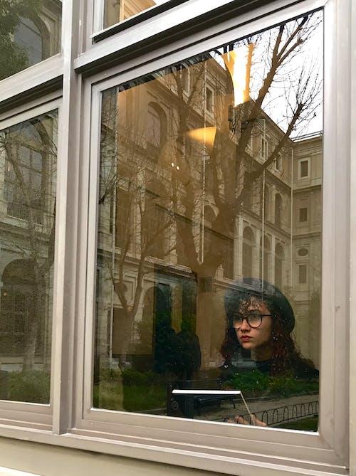 Женщина в черной куртке стоит у стеклянного окна