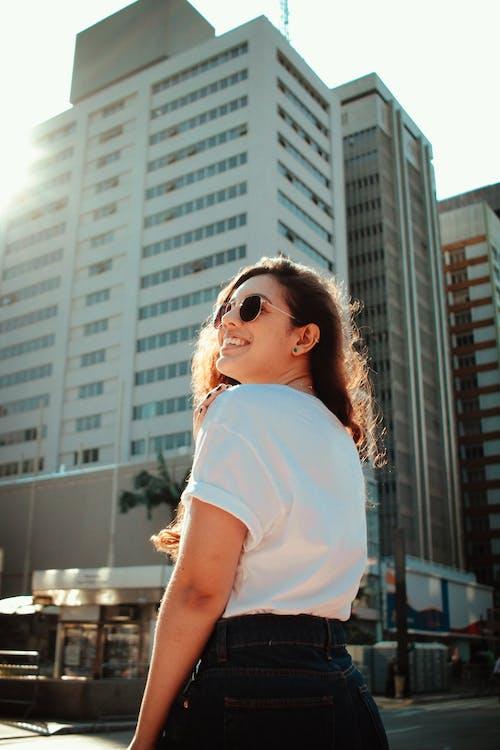 Gratis lagerfoto af afslappet, ansigtsudtryk, brunette, bygninger