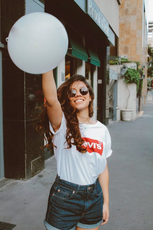 Woman in White Shirt Holding White Balloon