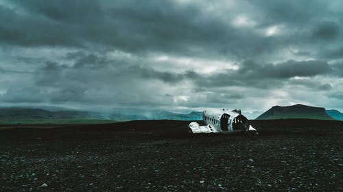 Airplane Wreck in Black Sand Under Gray Cloudy Sky