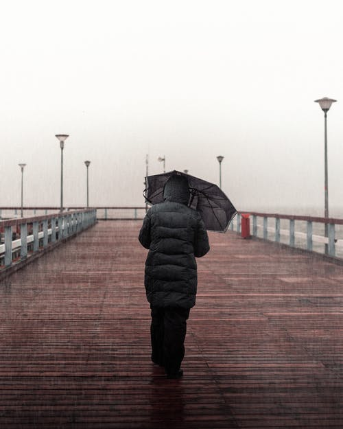 Person Wearing Black Jacket and Black Pants Holding Umbrella Walking on Boardwalk