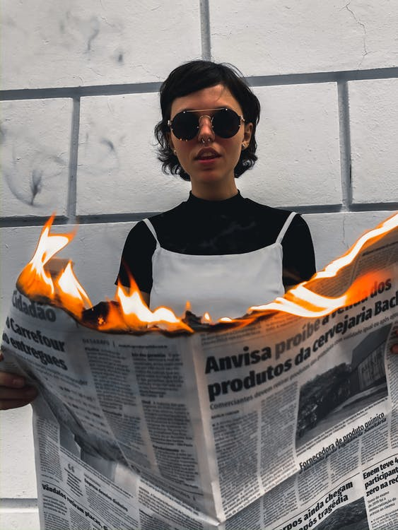 Woman in Black and White Tank Top Wearing Sunglasses While Holding Burning Newspaper
