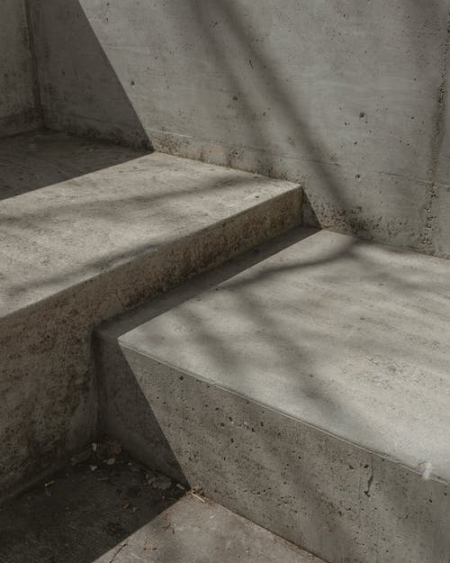 Shadows on old grey shabby dirty foot of outside unequal stairway in sunlight