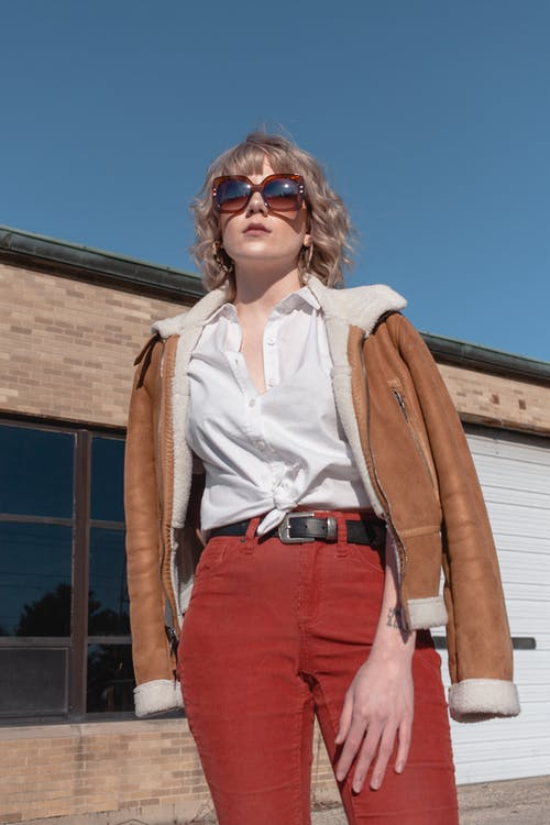 Woman Wearing White Top, Red Pants and Brown Jacket
