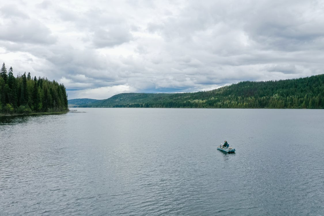 Person Riding A Boat On Lake