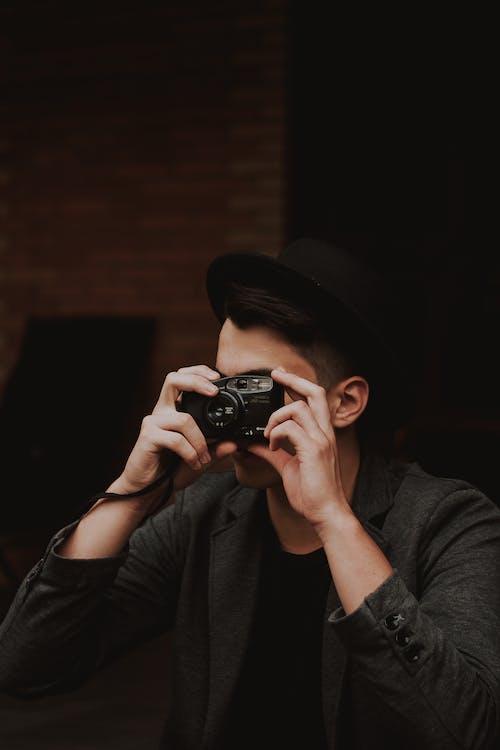 Man In Black Coat Holding Black Camera