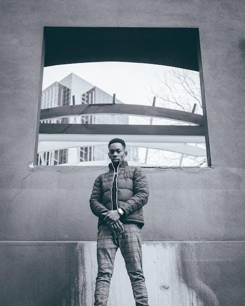 Man In Black Jacket Standing Beside Concrete Wall