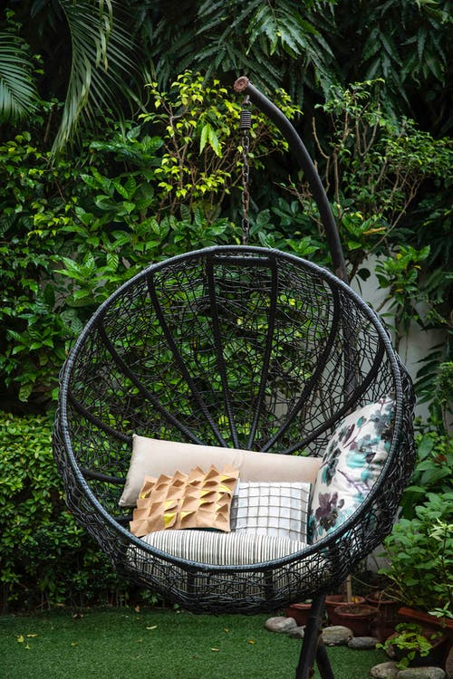 Black Metal Framed Round Basket With Brown and White Throw Pillows