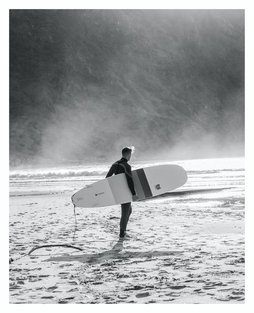 Grayscale Photo of Man Holding Surfboard Walking On Beach
