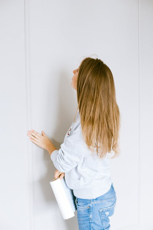 Woman In A Hoodie Touching Wall