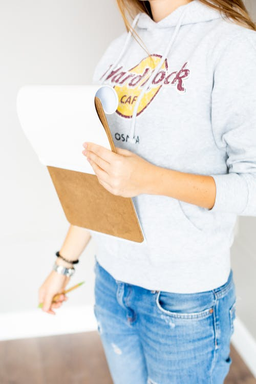 Person Wearing Gray Hoodie While Holding a Notepad