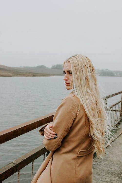 Woman in Brown Coat Standing on Bridge