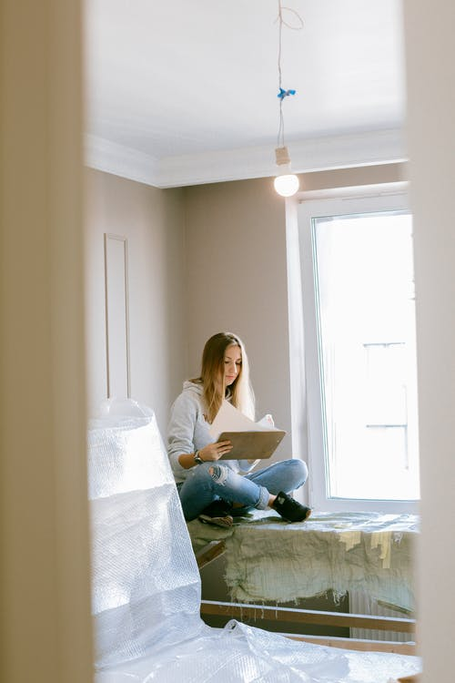 Photo of Woman Reading a Notepad