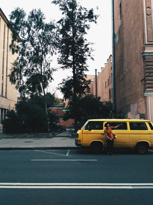 Person Standing Near Yellow Van on Road