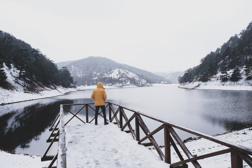 Back View of a Person in Yellow Jacket Standing A Deck By The River