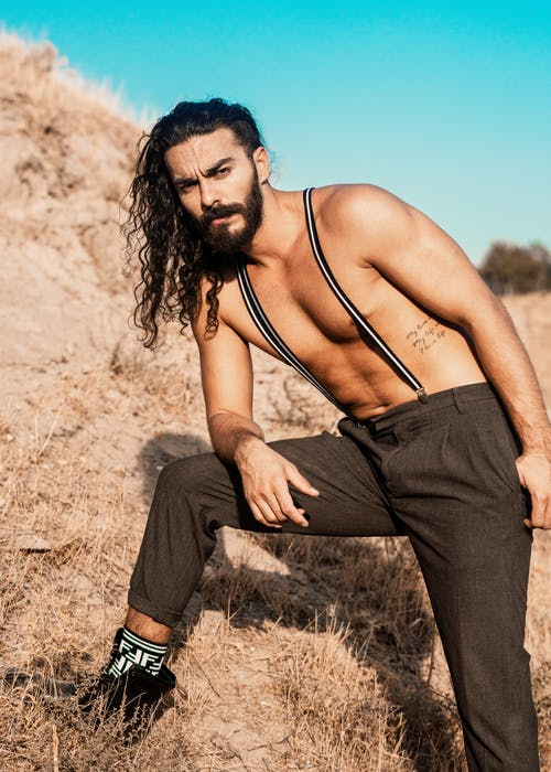 A Shirtless Man With Long Hair Wearing Suspender Outdoors