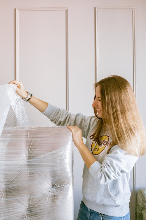 Woman Removing the Plastic Wrap of a Furniture