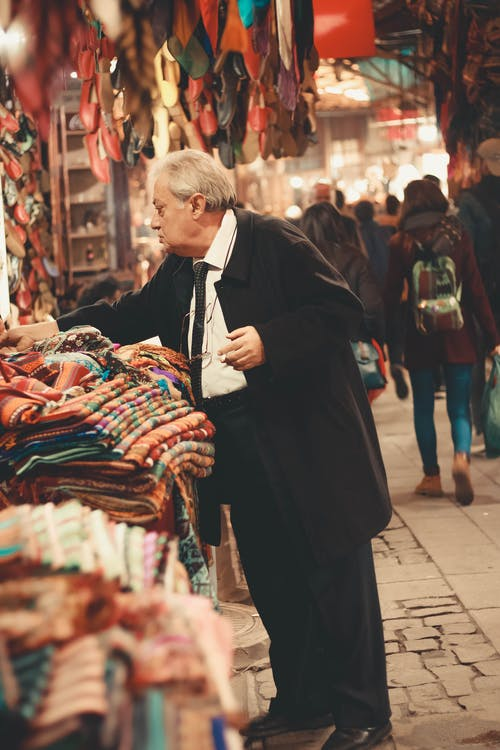Man in Black Coat Standing Near Clothes Display