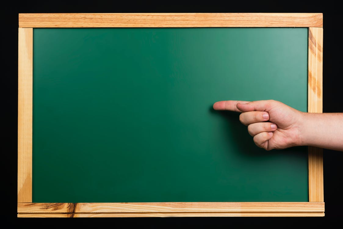 Persons Hand on Green Board